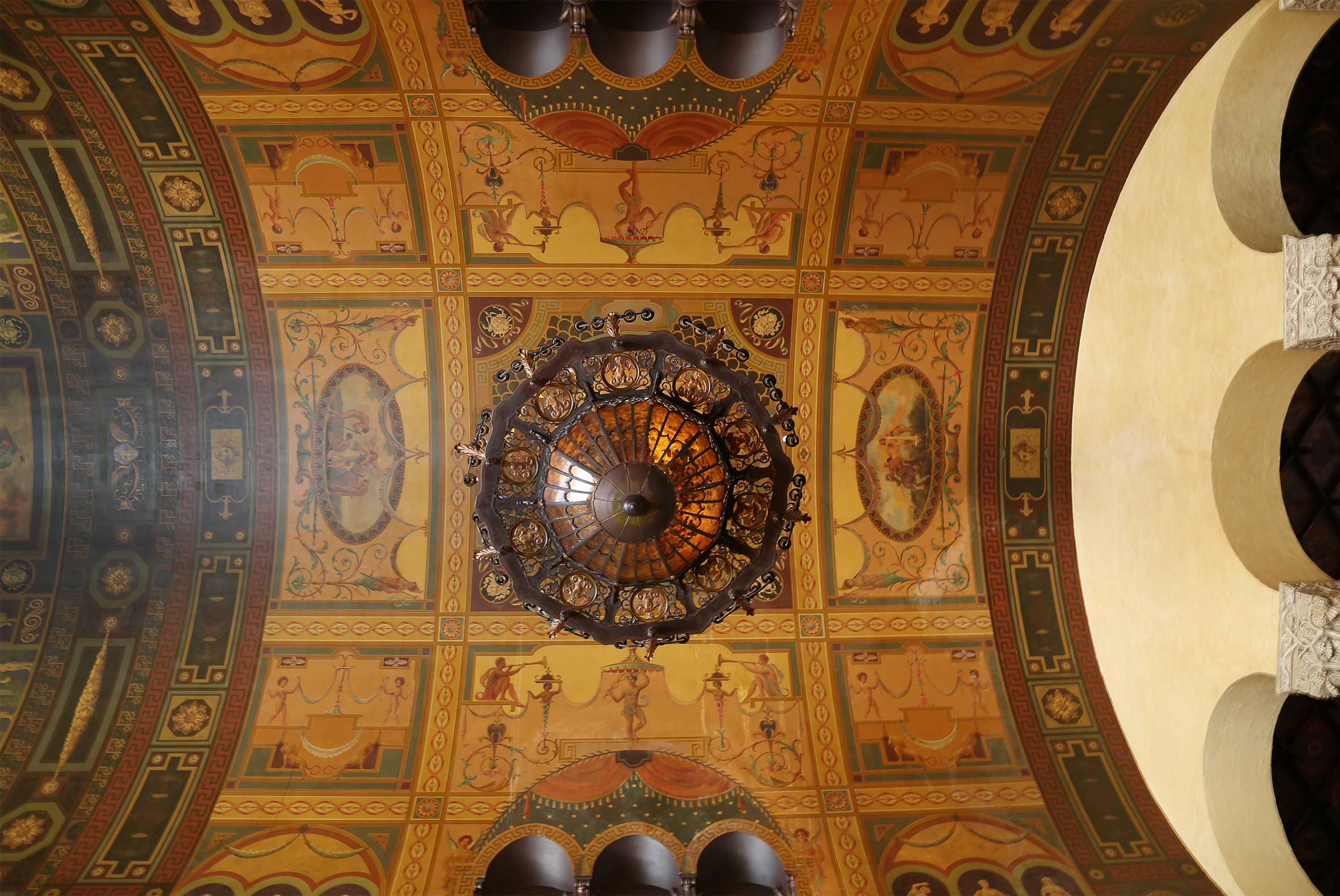 Looking up at historic painted ceiling and chandelier of The MacArthur Lobby - Los Angeles