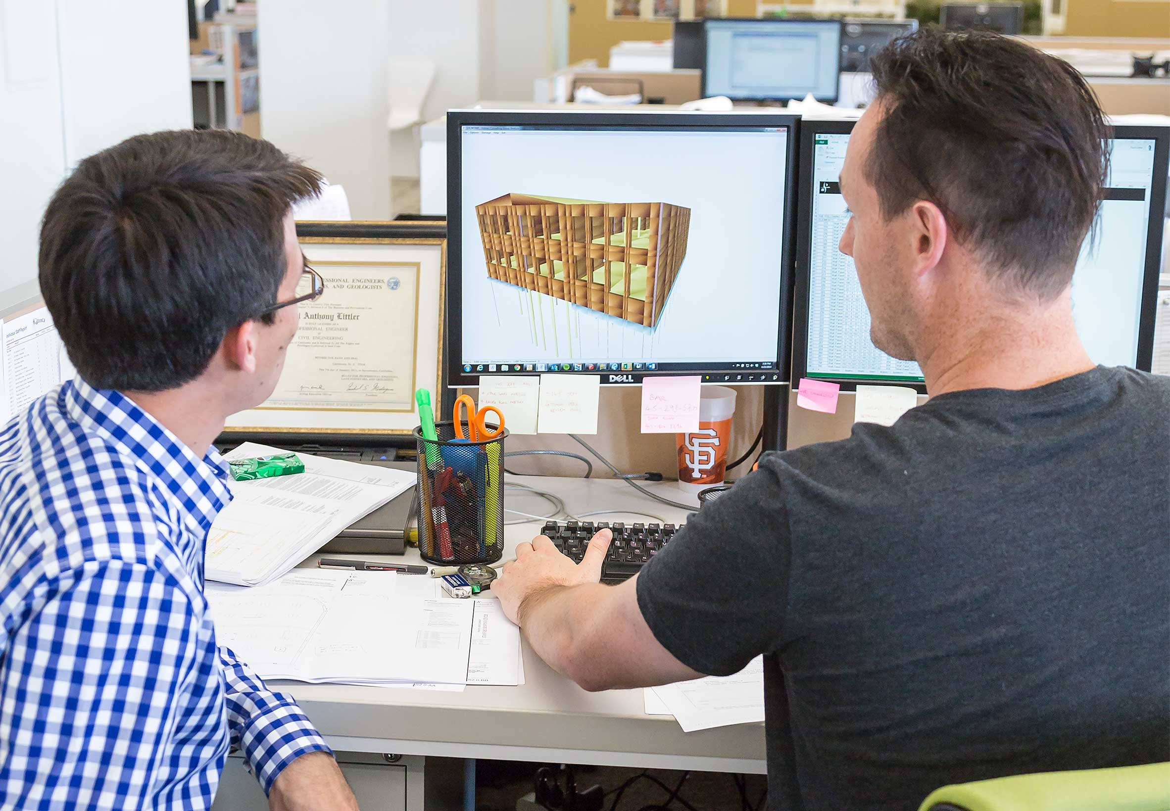 Engineers Review a 3D Building Model on Computer at Desk