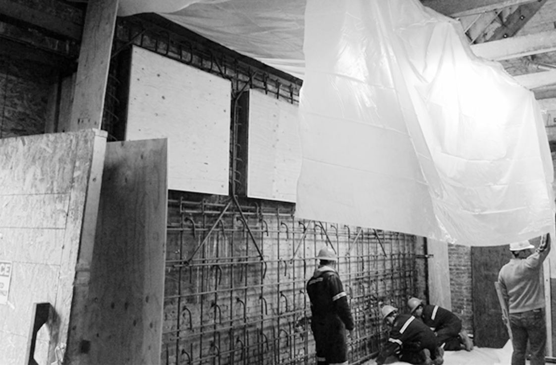 Shear Wall Installation Within Existing URM Building with Workers
