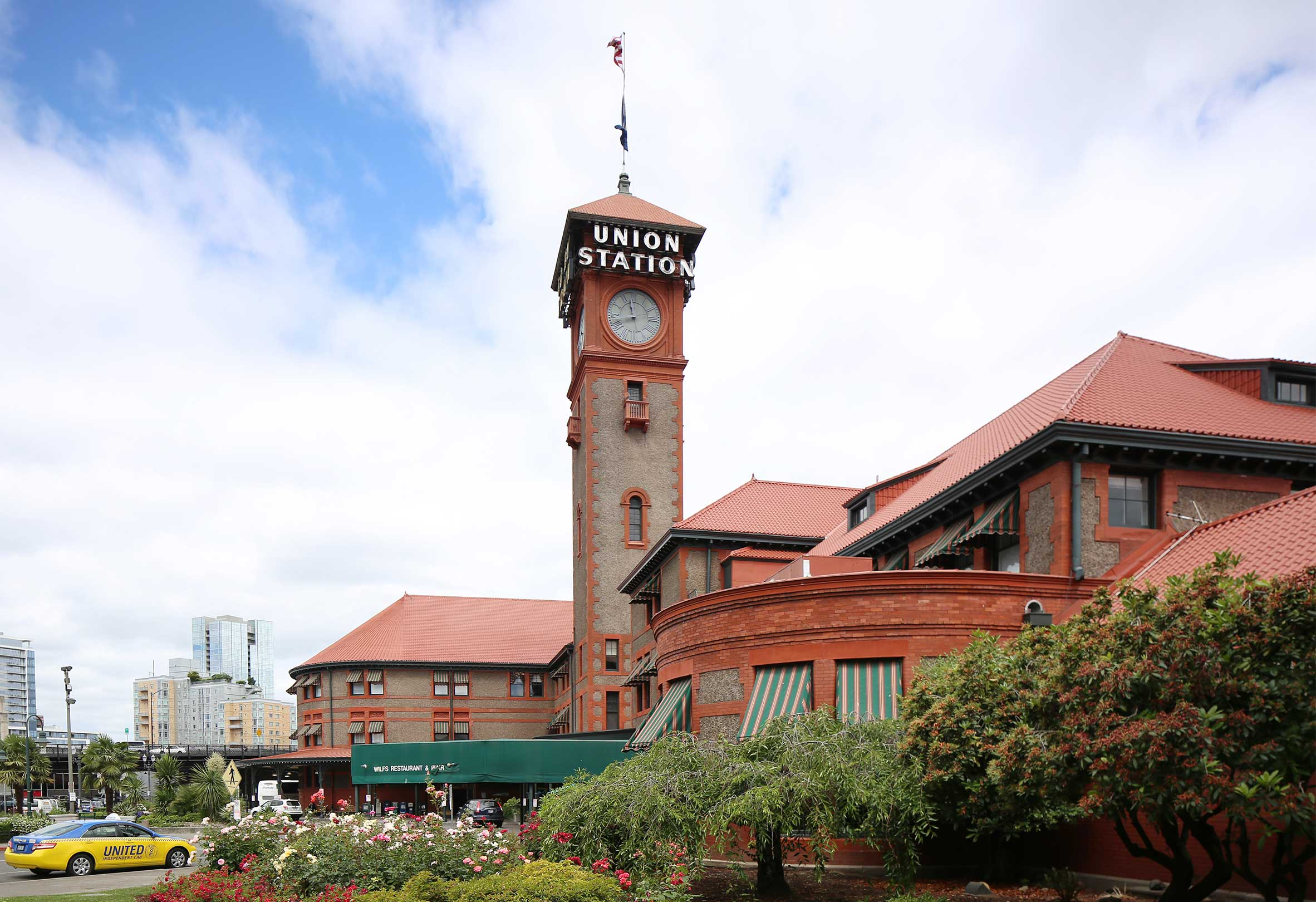 Entrance to Portland Union Station in Portland Oregon with gardens and blue sky